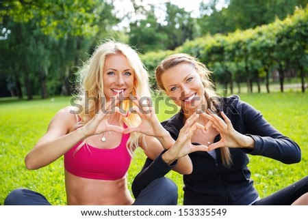 Young happy sporty girls showing heart sign with their hands on a meadow in a park - stock photo