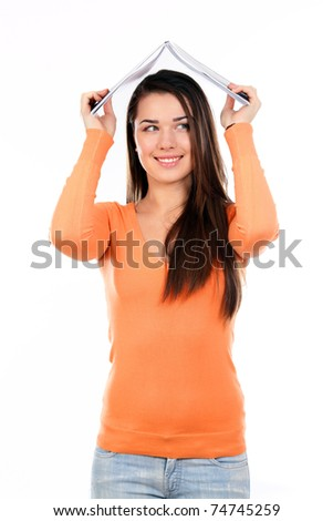 Young happy student holding a book making a roof over her head