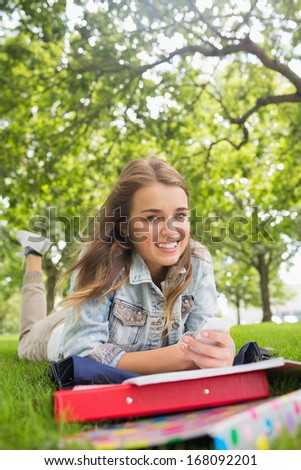 Young happy student lying on the grass sending a text on college campus - stock photo