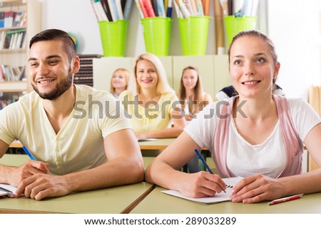 Young happy students studying in the classroom - stock photo