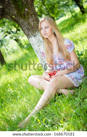 Young happy teen girl eating strawberry - stock photo