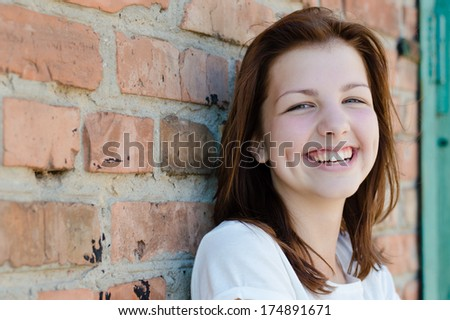 Young happy teenage girl standing at brick wall copyspace happy smiling & looking at camera  - stock photo