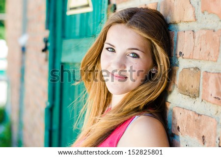 Young happy teenage girl standing at red brick wall background - stock photo