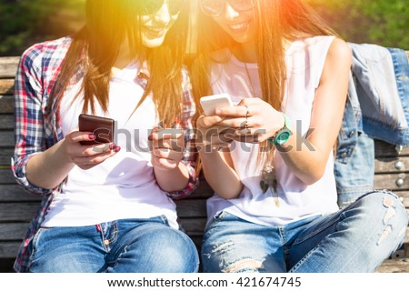 Young happy teenage girls using their phones and having fun in summer park. - stock photo