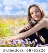 young happy teenager on the meadow with flowers - stock photo