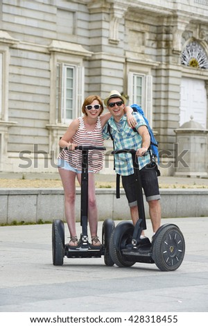 young happy tourist couple riding segway enjoying city tour in Madrid palace in Spain having fun driving together on funny and romantic summer holiday in urban transport concept - stock photo