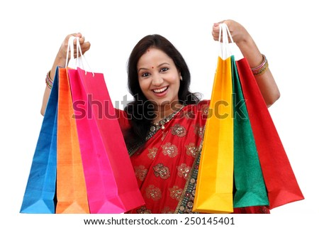 Young happy traditional woman with shopping bags - stock photo