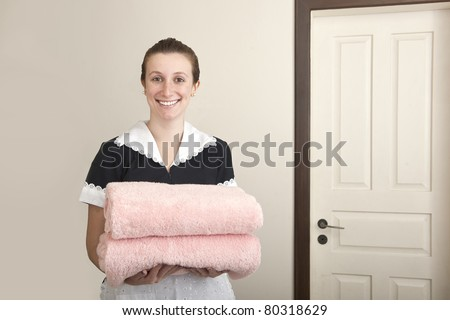 young happy uniformed maid carrying towels - stock photo