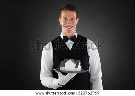 Young Happy Waiter Holding Tray With Miniature House - stock photo