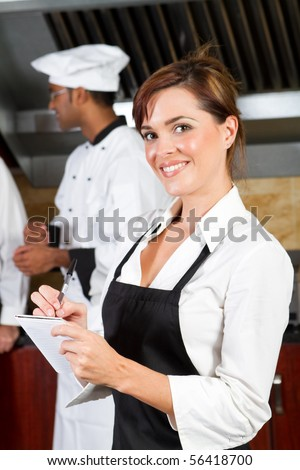 young happy waitress in restaurant kitchen with chefs behind - stock photo