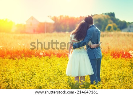 Young happy wedding couple hugging in the meadow back to camera and looking at their house. - stock photo