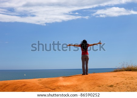 young happy woman at the coast with open arms - stock photo