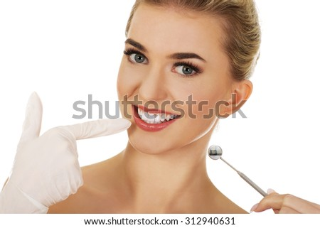 Young happy woman checking her teeth whith dental mirror,isolated on white - stock photo