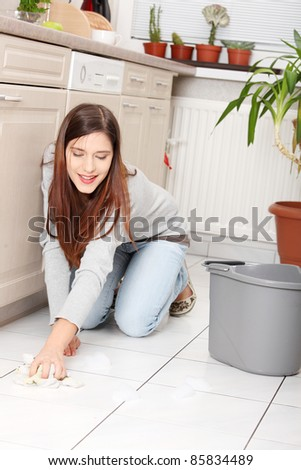 Young happy woman cleaning flor on her knees - stock photo