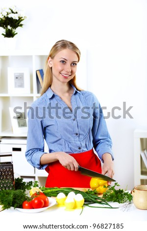 Young happy woman cooking fresh meal at home - stock photo