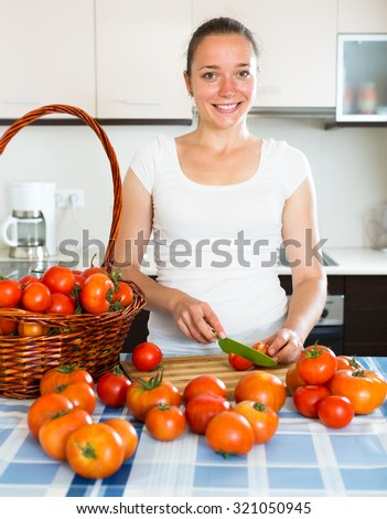 Young happy woman cooking tomatoes in the kitchen