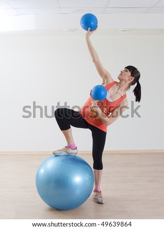 Young happy woman doing fitness exercises with ball