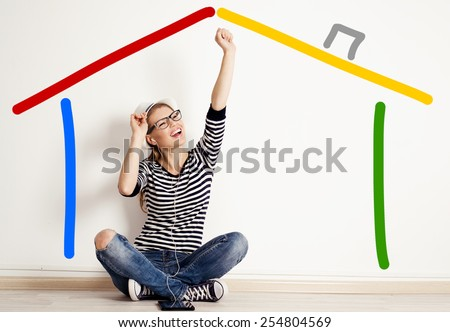 Young happy woman dreaming of new house sitting in empty room. Concept of mortgage, planning of new realty.  - stock photo
