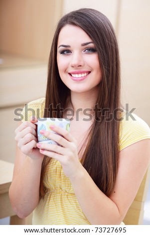 Young happy woman drinking a cup of tea - stock photo