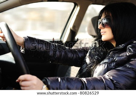 Young happy woman driving a car - stock photo