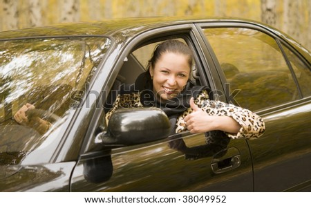young happy woman driving her new car