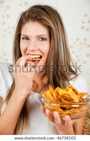 Young happy woman eating chips