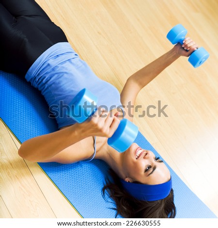 Young happy woman exercising with dumbbells at home