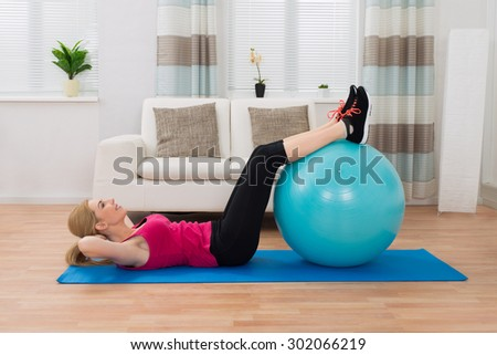 Young Happy Woman Exercising With Fitness Ball On Exercise Mat In Living Room