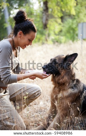Young happy woman givin water to her dog - stock photo
