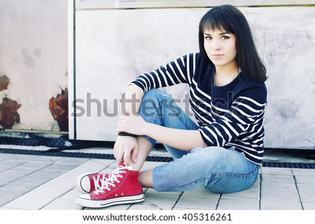 Young happy woman having fun outdoor. Beauty teenage girl   traveler woman. Fashionable hipster posing in stylish casual clothes and shoes. Fashion of teens.