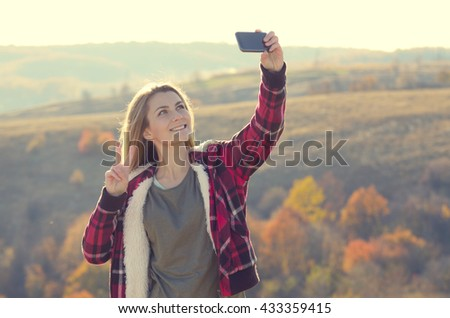 Young happy woman having fun outdoors taking selfie standing on the top of the hill. Backpacking tourism concept