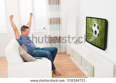 Young Happy Woman Having Fun While Watching Soccer Game On Television - stock photo