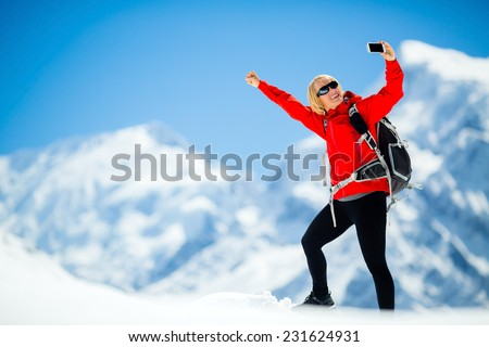 Young happy woman hiker selfie self-portrait on mountain peak summit in winter mountains Climbing inspiration and motivation beautiful landscape Fitness healthy lifestyle outdoors Himalayas Nepal - stock photo