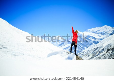 Young happy woman hiker successful on mountain peak summit in winter mountains. Climbing inspiration and motivation beautiful landscape. Fitness healthy lifestyle outdoors on snow in Himalayas, Nepal. - stock photo