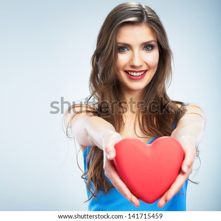 Young happy woman hold Love symbol red heart. Isolated on studio background female model. - stock photo