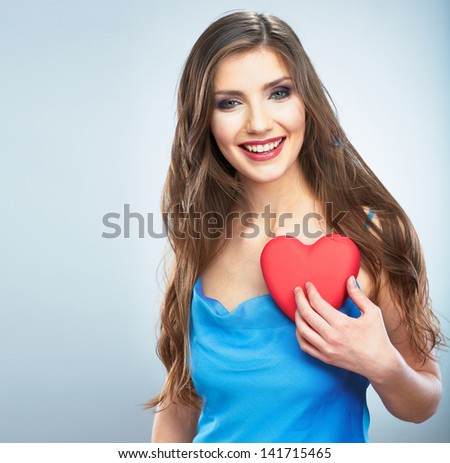 Young happy woman hold Love symbol red heart. Isolated on studio background female model.