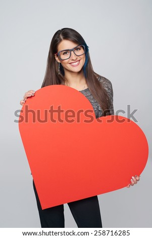 Young happy woman holdin Love symbol - big red heart shape - stock photo