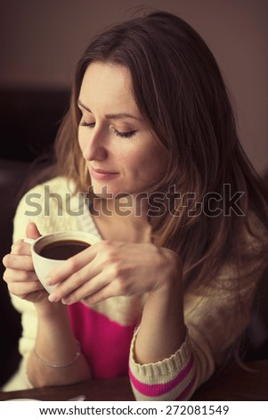 Young happy woman holding a cup of hot coffee or tea sits in a cafe, lifestyle, breakfast or dinner to spend time relaxing, healthy lifestyle, fashion, in a yellow sweater. - stock photo