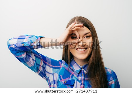 Young happy woman holding her hand over her eye as glasses and  looking through fingers - stock photo