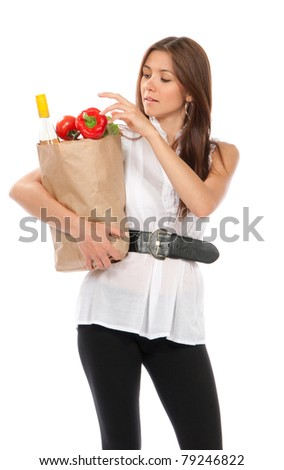 Young happy woman holding shopping paper bag full of vegetarian groceries, red pepper, salad, bottle of dry wine, mango isolated on white background - stock photo