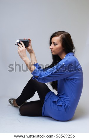 Young happy woman holding small video camera.at white background - stock photo