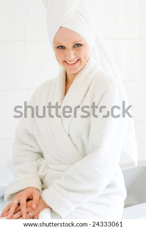 young happy woman in bathrobe in bathroom - stock photo