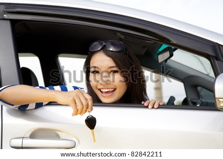 young happy woman in car showing the keys - stock photo