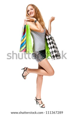Young happy woman in dress with colorful shopping bags on a white background