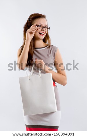 Young happy woman in dress with shopping bag on a white background