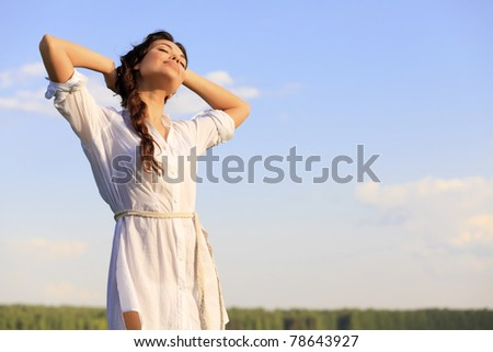 Young happy woman in green field - stock photo