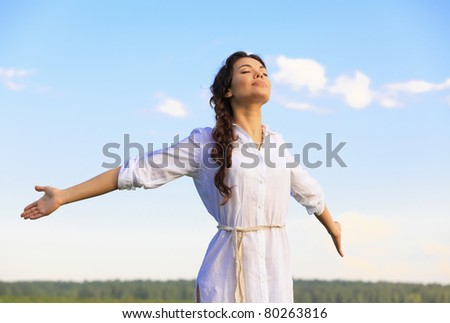 Young happy woman in green field, evening light - stock photo