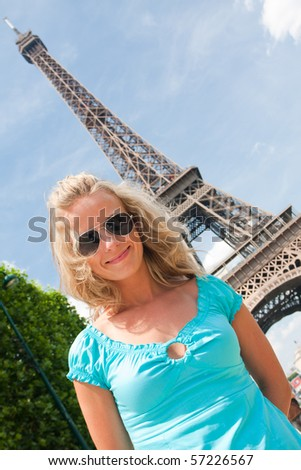 Young happy woman in Paris with Eiffel tower in background - stock photo