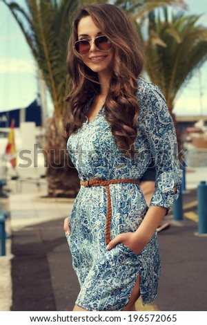 Young happy woman in stylish blue dress walking along the street on a sunny summer day. Outdoor fashion portrait of trendy girl.