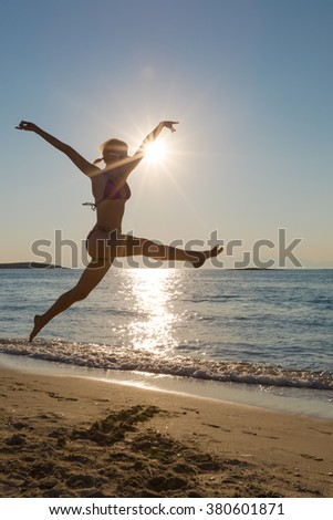 Young happy woman in swimsuit on the beach running and jumping on the seashore. Shot taken in backlit.